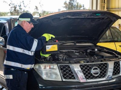 A mechanic in Gladstone inserting a new car battery into a Nissan - GMW Mechanical & Towing